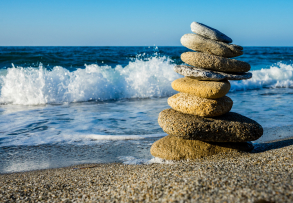 Rocks stacked on beach in front of the ocean waves